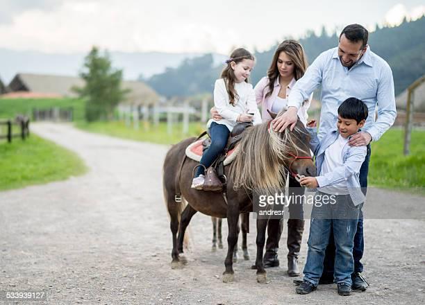 Family stroking a pony
