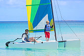 family of two, father and son, enjoying sailing together at hobie cat catamaran, active healthy lifestyle