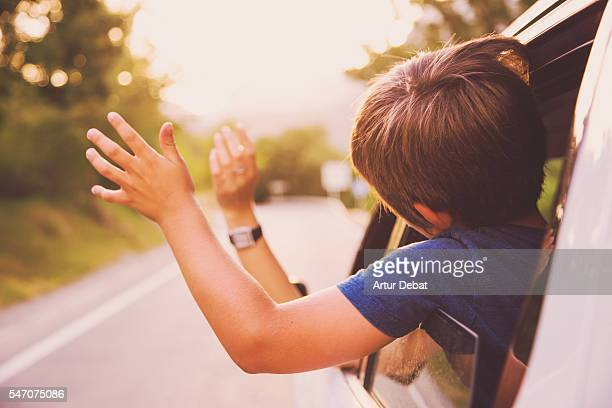 Family summer trip driving by suv car enjoying the road in the Catalan Pyrenees with hands on the road breeze.