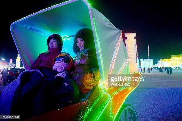 A family take a carriage as they visit the China Ice and Snow World during the Harbin International Ice and Snow Festival in Harbin northeast China's...