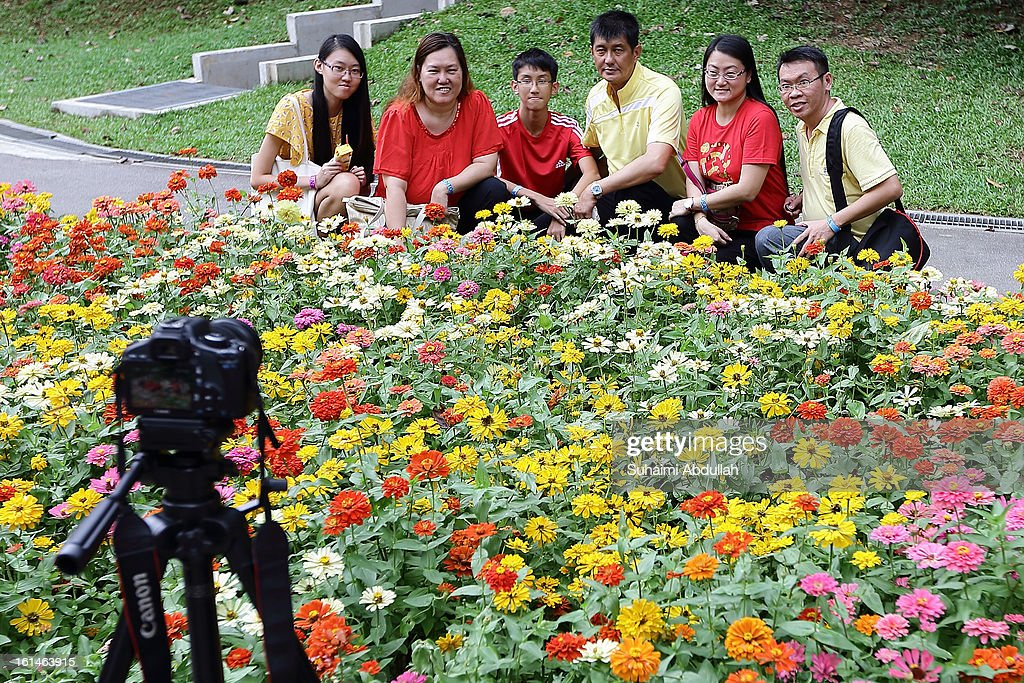 A family take a self portrait photograph in front of a flower display at the Sentosa Flowers exhibition at Palawan Beach on February 11, 2013 in Singapore. Millions of spring flowers decorate the island in celebration of the Chinese New Year, the year of the Snake.