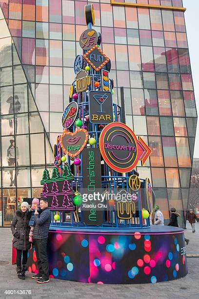 A family take pictures in front of a Christmas tree sculpture in Sanlitun Village which is a famous shopping street in Beijing on December 8 2014 in...