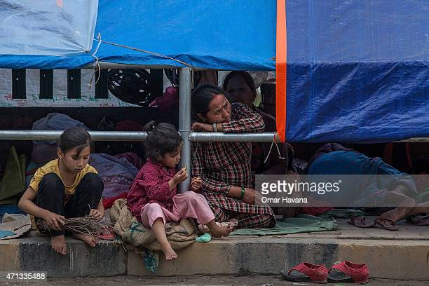 A family take shelter on a sidewalk in the city centre on April 27 2015 in Kathmandu Nepal A major 78 earthquake hit Kathmandu midday on Saturday and...