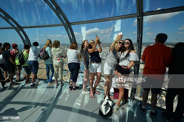 A family takes a selfie inside the British Airways i360 viewing platform in Brighton southern England on August 26 2016 People in much of Britain...