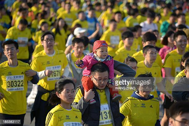 A family takes part at the start of the Beijing Marathon in the Chinese capital on October 20 2013 A total of 30000 runners took part in the race AFP...