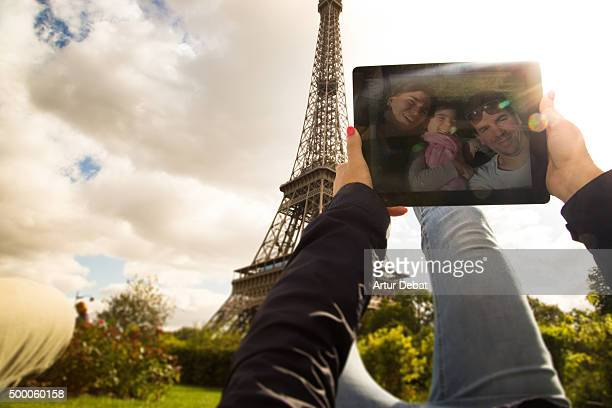 Family taking a selfie with digital tablet in the Tour Eiffel.