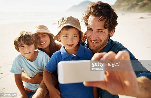 Familie nehmen Foto von sich selbst am Strand