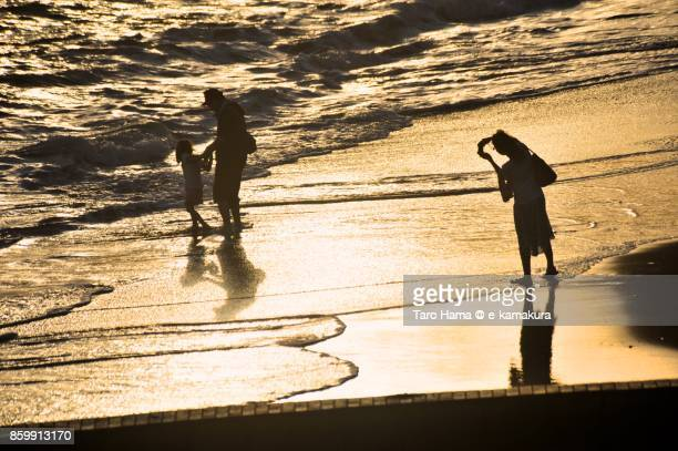 A family taking photos on the sunset beach in Kamakura city in Kanagawa prefecture in Japan