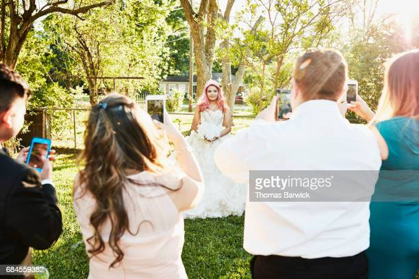 Family taking photos with smartphones of young woman in quinceanera gown in backyard