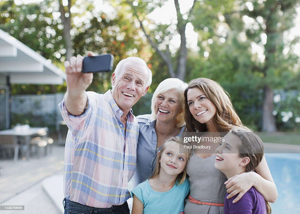 Family taking picture of themselves outdoors : Stock Photo
