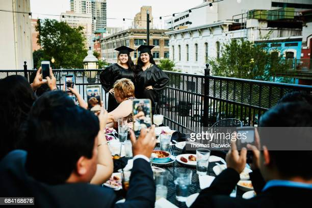 Family taking picture of two female graduates during meal on restaurant deck