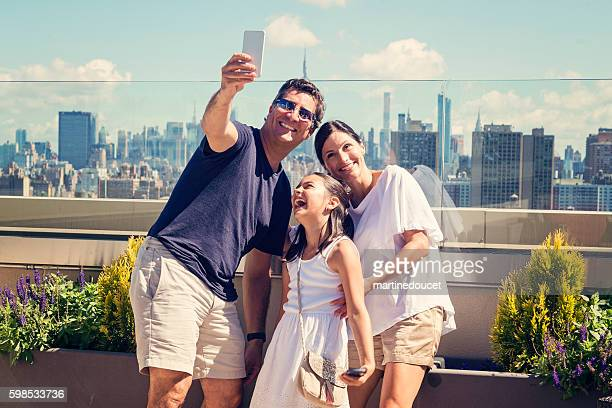 Family taking selfie on a rooftop with New-York skyline.