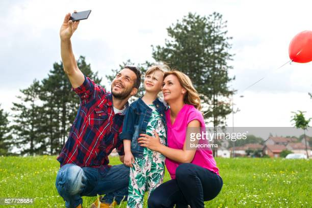 Family taking selfie with smartphone in nature