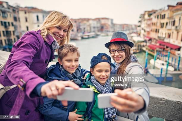 Family taking selfies on Rialto Bridge, Venice, Italy