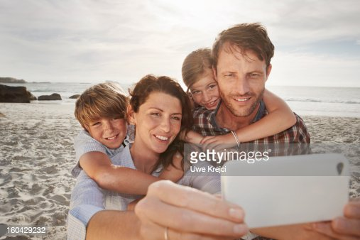 Family taking self-portrait with smart phone : Stock Photo