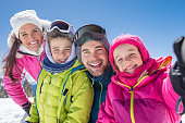 Happy family taking selfie in snowy mountain during winter holiday. Daughter taking a picture of family on the alps while looking at camera. Happy mother and father with children posing for a selfie.