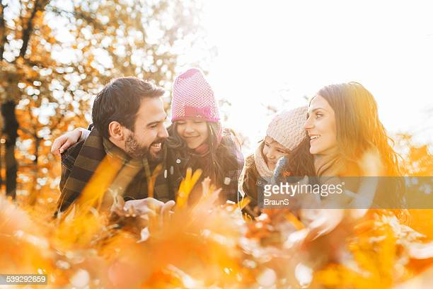 Family talking in grass during autumn day.