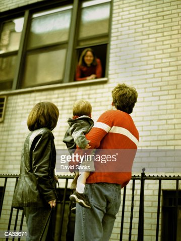 Family talking to woman in window : Stock Photo