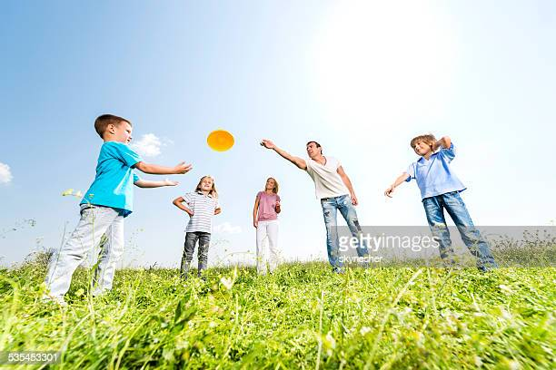 Family throwing Frisbee outdoors.