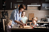 Family time: Mom with three children preparing cookies in the kitchen. Real authentic family. Portrait.