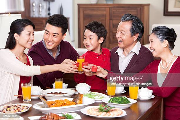 Family toasting at dinner table during Chinese New Year