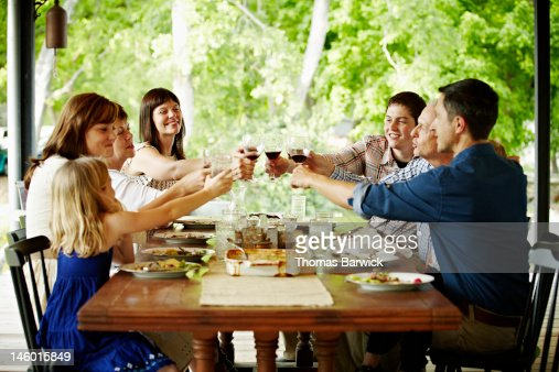 Family toasting at dinner table outdoors on porch : Stock Photo