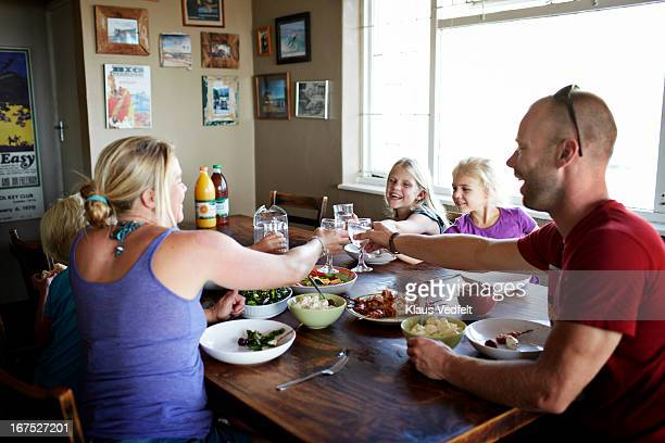 Family toasting at dinner table