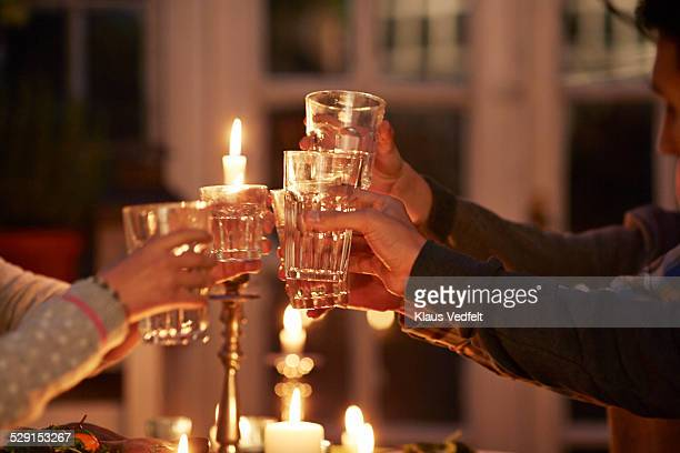 Family toasting at dinner with candle lights