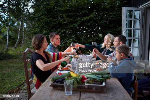 Family toasting at outside dinner table