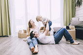 Family together happy young beautiful with a little baby moves with boxes to a new home