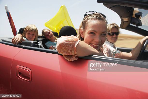 Family travelling in convertible car, smiling, portrait