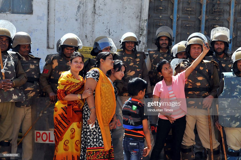 A family trying to get a selfie with police forces deployed outside the Bhojshala on February 11, 2016 in Dhar, India. A communal flare-up is feared in the otherwise peaceful town of Dhar, Madhya Pradesh, on Friday, February 12. The contested site is the Kamal-al-Din congregational mosque of Dhar, protected by the Archaeolgical Survey of India, which allows Muslims to offer jummah or Friday prayers. Hindus are allowed entry in the monument to offer prayers on Tuesdays and conduct a special puja on the occasion of Basant Panchami. This week, however, the Friday prayers coincide with the festival of Basant Panchami.