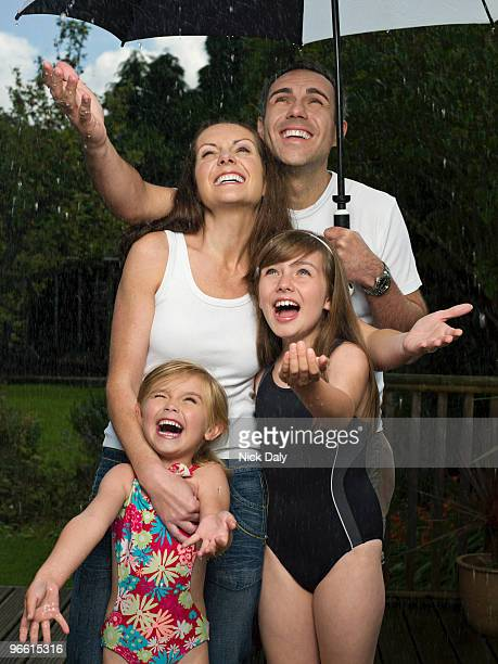 A family under an umbrella in the rain