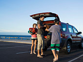 Family unloading back of vehicle at beach