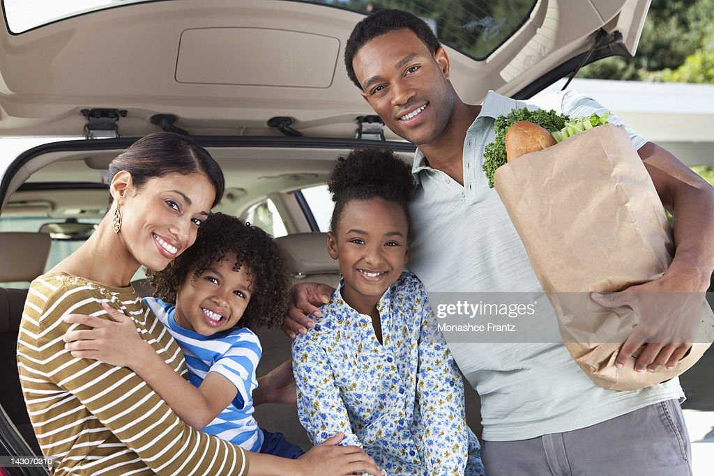 Family unloading groceries from car : Stock Photo