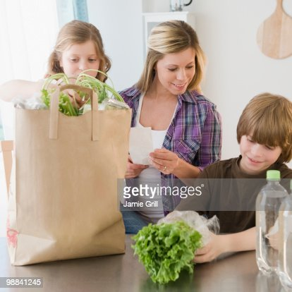 Family unloading groceries while checking receipt
