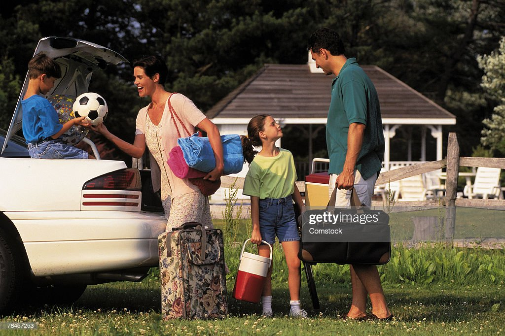 Family unpacking car for vacation