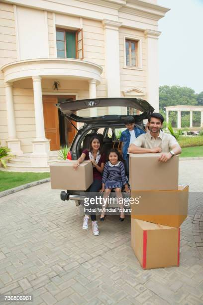 Family unpacking cardboard boxes from car