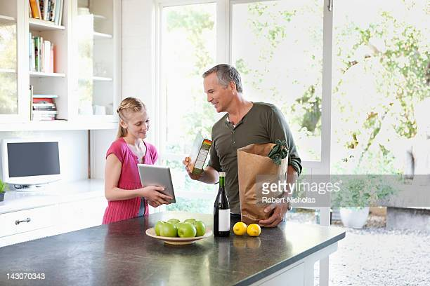Family unpacking groceries in kitchen