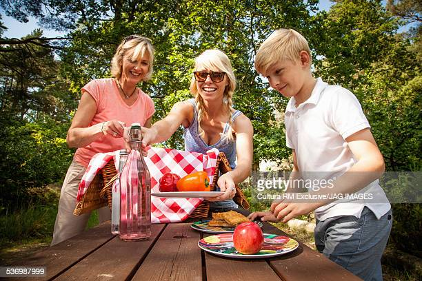 Family unpacking picnic basket in forest