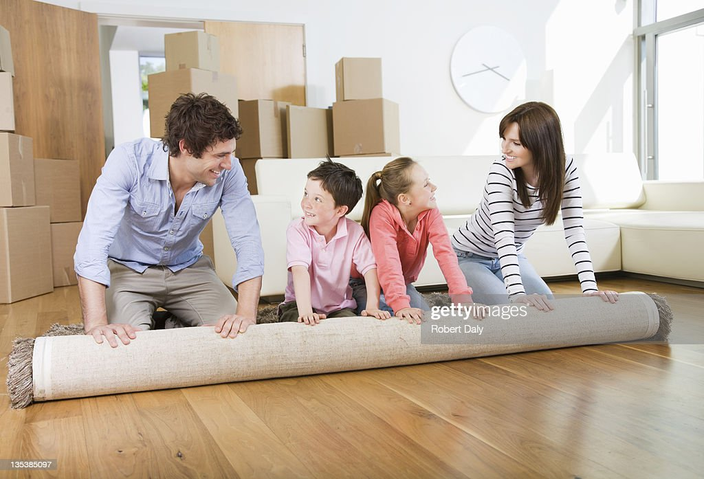 Family unrolling carpet together in new home : Stock Photo