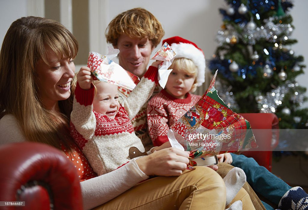 Family unwrapping Christmas presents on sofa. : Stock Photo