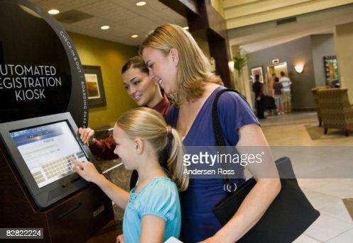 Family using a hotel kiosk : Stock Photo