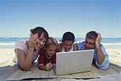 Family using a laptop on the beach