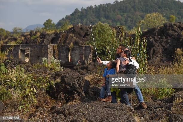 Family using a selfie stick at the ruins of a lavaburied church near the Paricutin Volcano in Michoacán México