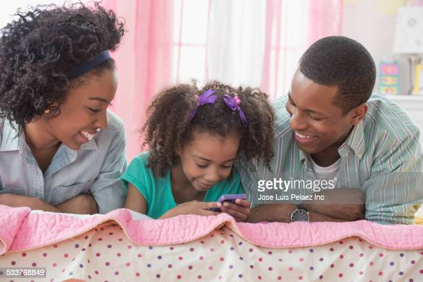 Family using cell phone together on bed