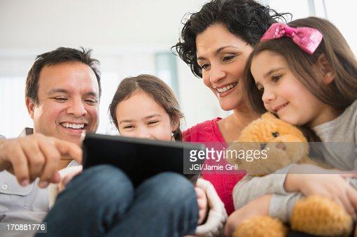Family using digital tablet together on sofa : Stock Photo