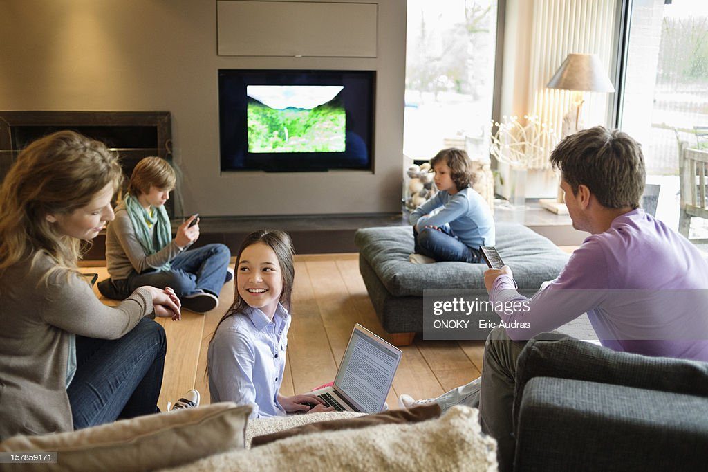 Family using electronic gadgets in a living room : Stock Photo