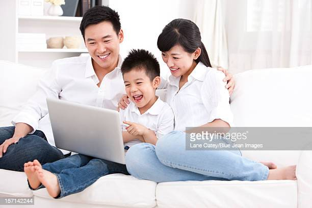 Family using laptop in sofa
