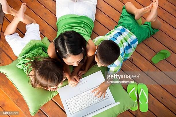 Famille à l'aide d'un ordinateur portable sur la terrasse